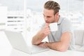 Focused businessman holding cup while using laptop in his office Royalty Free Stock Image