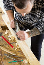 Focused craftsman working with plane on wood plank in workshop Royalty Free Stock Photo