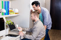 Focused gay couple looking at papers in office Royalty Free Stock Image