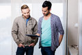 Focused gay couple looking at tablet home Royalty Free Stock Image