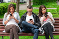 Focused group of friends looking on their phones and not socializing two women one man sitting a bench in park separately at Stock Image