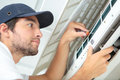Focused handyman testing air conditioning on wall Royalty Free Stock Photo