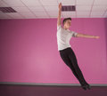 Focused male ballet dancer leaping up in the dance studio Stock Photography