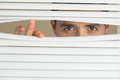 Focused male eyes spying through roller blind beautiful brown Royalty Free Stock Photo