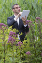 Focused male mad botanist working and searching on tablet outside usage outdoors fun scientist or with wireless standing alone in Royalty Free Stock Image
