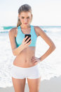 Focused slender blonde in sportswear texting on a sunny beach Stock Images