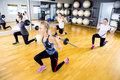 Focused team do split squats with weights at fitness gym Royalty Free Stock Photo