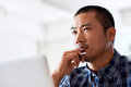 Focused young Asian designer deep in thought at work Royalty Free Stock Photo