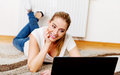 Focused young woman using laptop while lying on floor Royalty Free Stock Photo