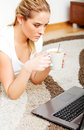Focused young woman using laptop while lying on floor and drinking coffee Royalty Free Stock Photo