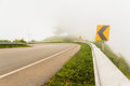 Fog and traffic signs on backcountry curve road Royalty Free Stock Image