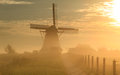 Foggy dutch sunrise autumn in the countryside near a windmill Royalty Free Stock Image