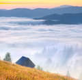 Foggy landscape with an old barn in the mountains in summer Royalty Free Stock Photo