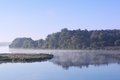 Foggy landscape with tree silhouette and reflection on water on fog at sunrise.Early summer morning on tranquil lake.Morning Lake. Royalty Free Stock Photo