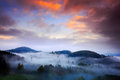 Foggy morning with beautiful orange clouds. Cold misty foggy morning in a fall valley of Bohemian Switzerland park. Hills with fog Royalty Free Stock Photo