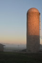 Foggy silo sunrise warm light an a farm site Stock Image