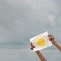 Foglio di carta con l immagine del sole contro il cielo nuvoloso Immagini Stock Libere da Diritti