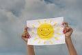 Foglio di carta con l immagine del sole contro il cielo nuvoloso Fotografia Stock