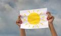 Foglio di carta con l immagine del sole contro il cielo nuvoloso Immagini Stock