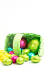 Foil wrapped easter eggs spilling green wicker basket Royalty Free Stock Photography