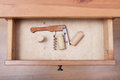 Foldable corkscrew and corks in open drawer Royalty Free Stock Photo