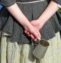Folded hands of colonial woman holding a tin cup Stock Photos