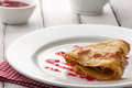 Folded pancake on white plate light summer breakfast with hot and raspberry jam Stock Photos