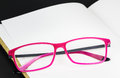 Folded pink glasses on book Royalty Free Stock Photo