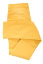 Folded yellow jeans are on white Royalty Free Stock Image
