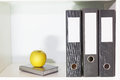 Folders for documents, planner and green apple on a book shelf Royalty Free Stock Photo