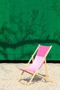 Folding chair in front of green wall on gravel Royalty Free Stock Photos
