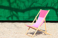 Folding chair in front of green wall on gravel Royalty Free Stock Photo