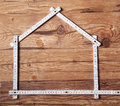 Folding Ruler Forming a House on Wooden Table Royalty Free Stock Photo