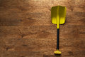Folding small yellow shovel lying on  wooden floor Royalty Free Stock Photo