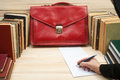 Follow the law. Professional lawyer sitting at the table and signing papers. On a wooden table books, documents, red briefcase. Co Royalty Free Stock Photo