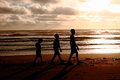 Follow the leader a silouette of three children walking in a line at beach Royalty Free Stock Images