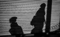 Follow me shadow black and white night photo of a of two persons are walking like a woman and a child boy or girl Stock Photo