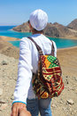 Follow me to the sea a woman with a colorful backbag heading to the sea with mountains in background Stock Photos