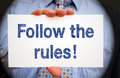 Follow the rules - Manager holding sign with text Royalty Free Stock Photo