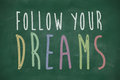 Follow your dreams phrase handwritten on blackboard Stock Images