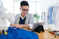 Following instructions young man on digital tablet when sewing Royalty Free Stock Photo