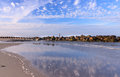 Folly beach coastal landscape south carolina of with water reflection displaying polka dot clouds in blue sky rocky boulders and Royalty Free Stock Photos