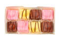 Fondant fancies fancy cakes in a box isolated against white Royalty Free Stock Photography