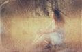 Fondo borroso surrealista de la mujer joven que se sienta en la piedra en concepto abstracto y soñador del bosque la imagen es Imagen de archivo libre de regalías