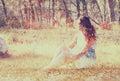 Fondo borroso surrealista de la mujer joven que se sienta en la piedra en concepto abstracto y soñador del bosque la imagen es Imagenes de archivo