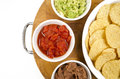 Food appetizers chips salsa refried beans guacamole wood cutting and on board Stock Images