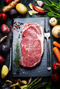 Food background with fresh vegetables and raw beef steak slate wood Royalty Free Stock Photo