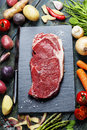Food background with fresh vegetables and raw beef steak slate wood Royalty Free Stock Photography