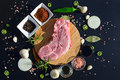 Food background. Meat on a cutting board and pepper, bay leaf, rosemary, onions, Himalayan salt, olive oil, soy sauce on a black b Royalty Free Stock Photo