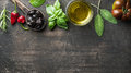 Food background with vegetables, herbs and condiment. Greek black olives, fresh basil, sage, rosemary, tomato, peppers Royalty Free Stock Photo